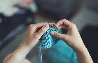Hands knitting a blue woollen square